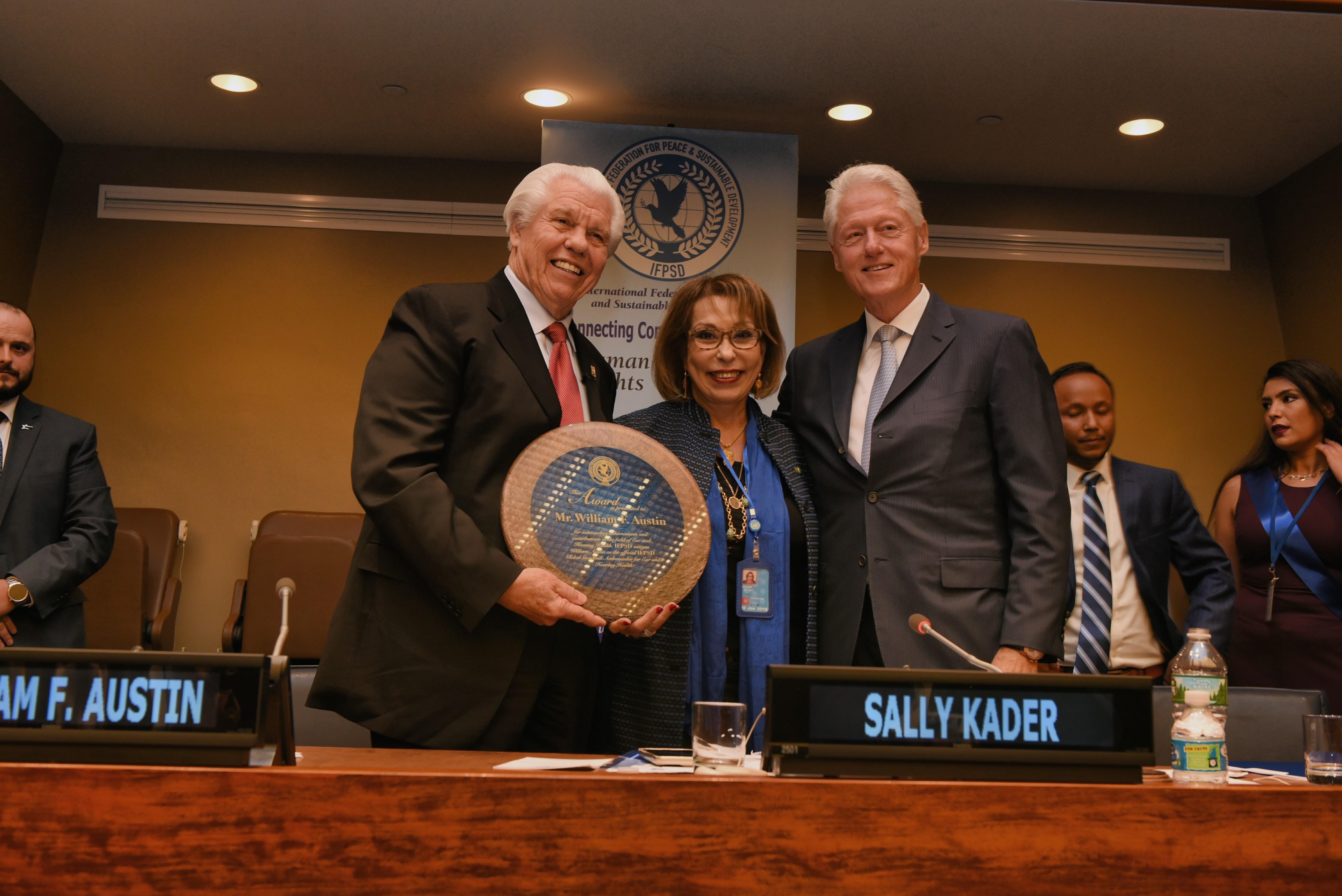 親善大使表彰を迎えて笑顔でカメラを見つめるビル・オースティンとビル・クリントン、そしてサリー