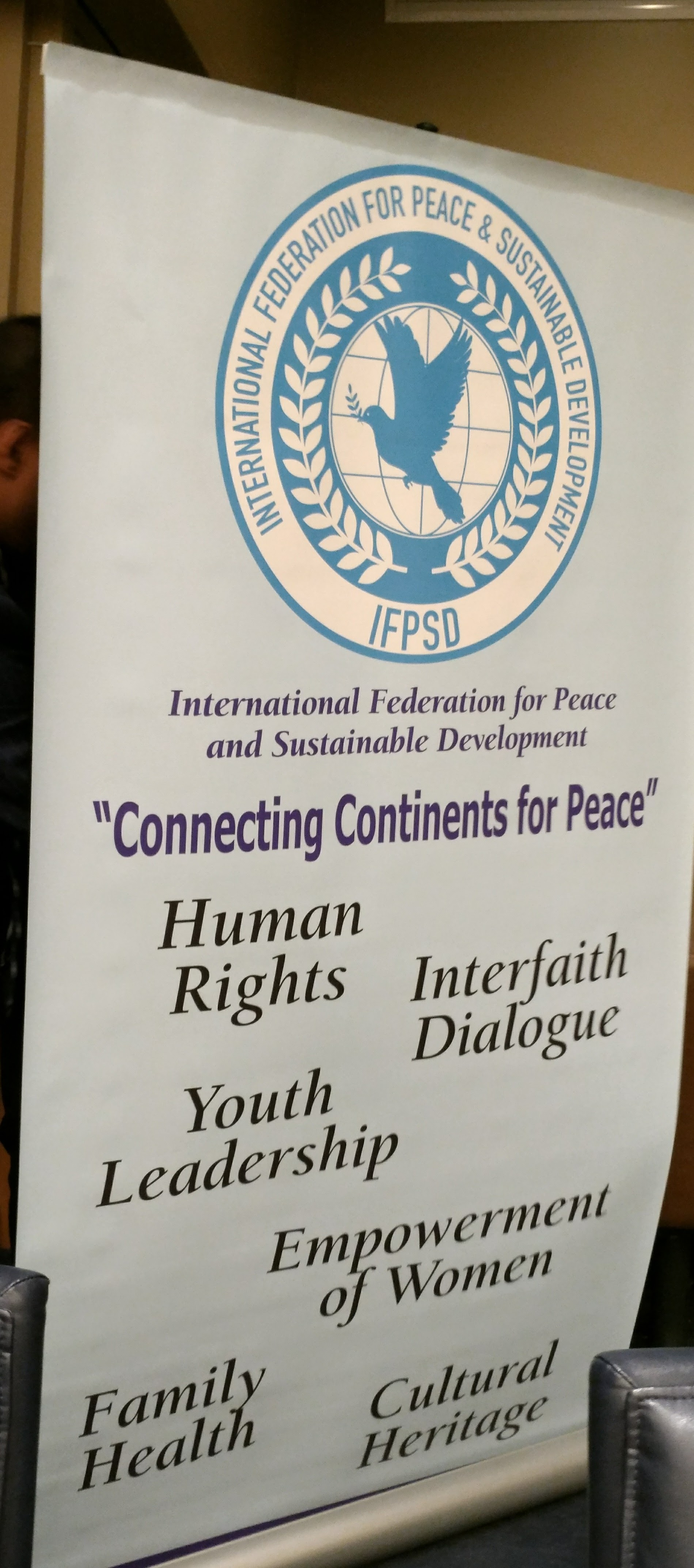 国連認証機関である平和と持続的開発に関する国際機関(IPSD)のバナーには人権、宗教観対話、若年層のリーダーシップ、女性の社会参加、家族の健康、文化遺産