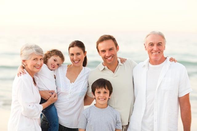 笑顔で海辺にたたずむ3世代家族のイメージ